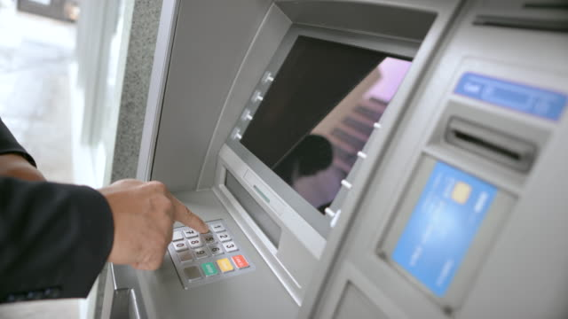ld man inserting bank card into atm slot and entering his pin number to make a withdrawal - inserting stock videos & royalty-free footage