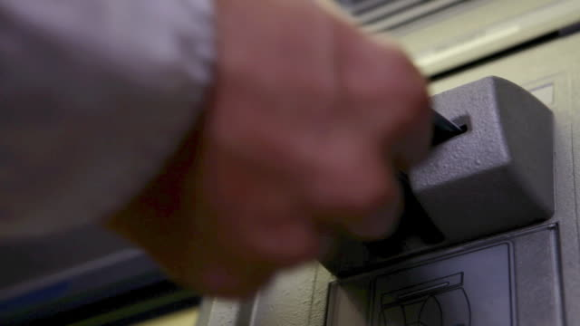Man inserting bank card into cash machine
