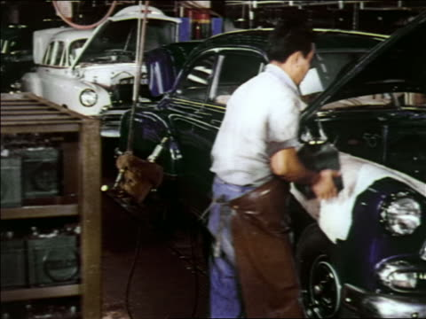 1951 pan man inserting battery into car engine on nearly completed car in assembly line / chevrolet - 1951 stock videos & royalty-free footage