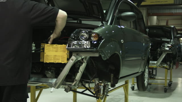 ms pan man inserting battery pack into front of electric car on assembly line, st. jerome, quebec, canada - baseballmütze stock-videos und b-roll-filmmaterial