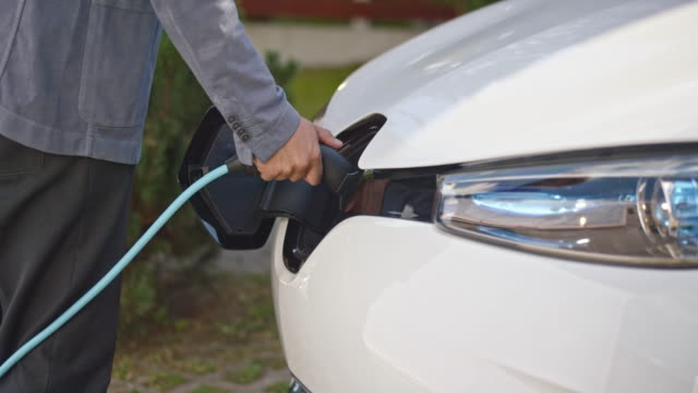 vídeos de stock e filmes b-roll de slo mo man inserting plug into electric car - environmental conservation
