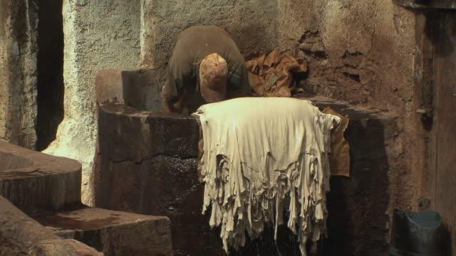 vídeos y material grabado en eventos de stock de ms man inside stone vessel pulling skins after dying, fez, morocco - encuadre de tres cuartos