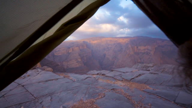 man inside tent looking out over canyon - tent stock videos and b-roll footage