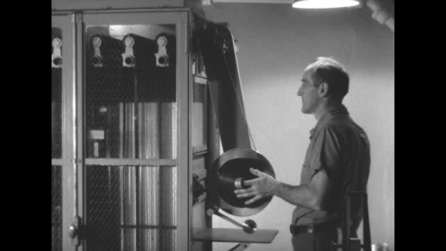 man inspecting filmmaking machine with flashlight / man loading film onto reel / film threading through machine / filmmaking machines / note exact... - film reel stock videos & royalty-free footage