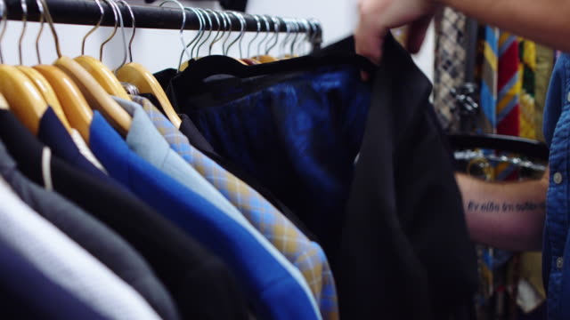man inspecting lining of vintage jacket - second hand stock videos & royalty-free footage