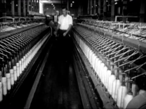 Man inspecting spools of yarn spinning on loom machine in factory / AUDIO