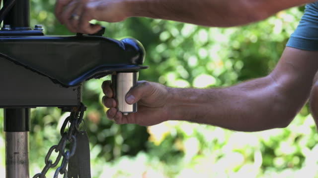 man installing camper trailer padlock during camping in summer - camper trailer stock videos and b-roll footage