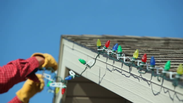 man installing led christmas lights onto a house roof - christmas lights stock videos & royalty-free footage