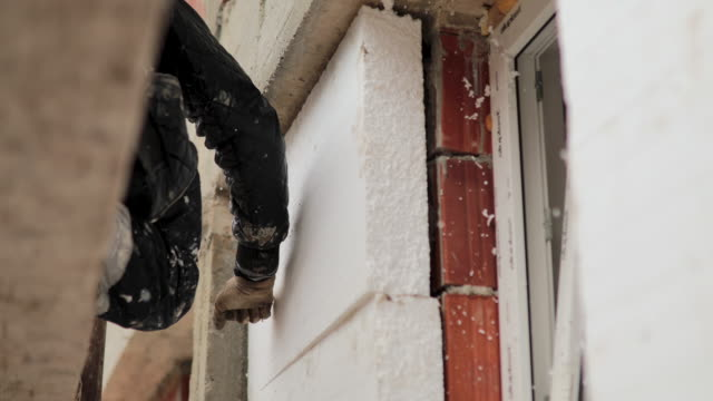 man installing styrofoam insulation board for energy saving on exterior wall of house - energy efficient stock videos & royalty-free footage