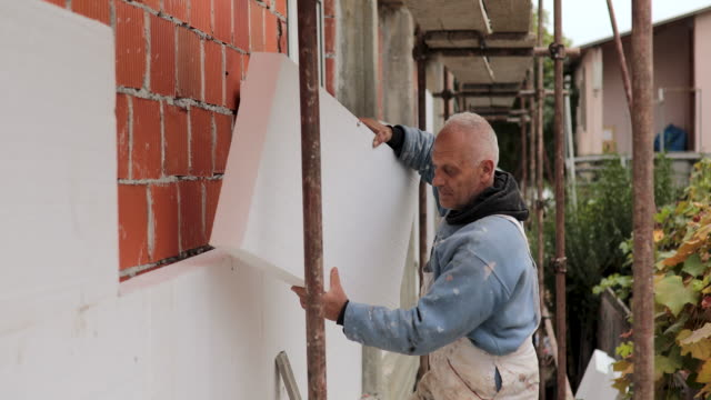 man installing styrofoam insulation board for energy saving on exterior wall of house - polystyrene stock videos & royalty-free footage