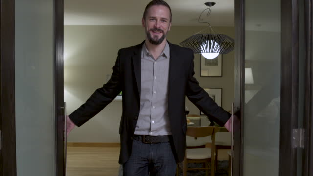 vidéos et rushes de man inviting guest to dinner table in domestic dining room. - embrasure de porte