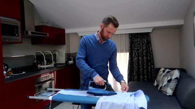 vídeos y material grabado en eventos de stock de hombre planchado una camisa azul - video stock - plancha