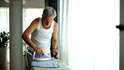 自宅でシャツにアイロンをかける男。 - アイロン台点の映像素材/bロール