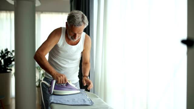 自宅でシャツにアイロンをかける男。 - アイロン点の映像素材/bロール