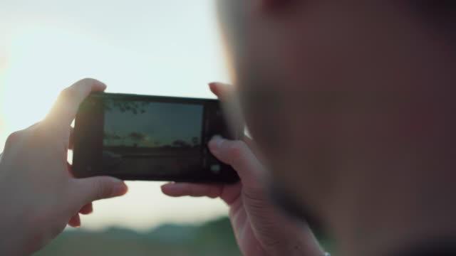 stockvideo's en b-roll-footage met een man is een live-uitzending van uw smartphone stock video - rug