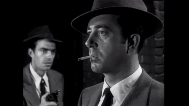 1952 a man is accosted by a gun wielding gangster, and then follows him down an alley - suspicion stock videos & royalty-free footage