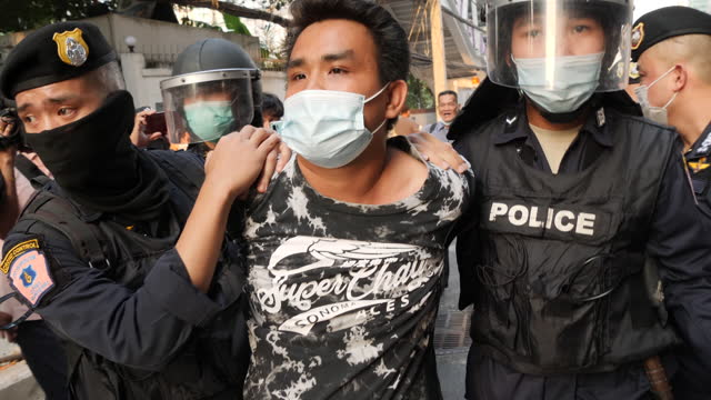 man is arrested during protests near the myanmar embassy on february 1, 2021 in bangkok, thailand. protesters were angry at the recent coup d'etat in... - ミャンマー点の映像素材/bロール