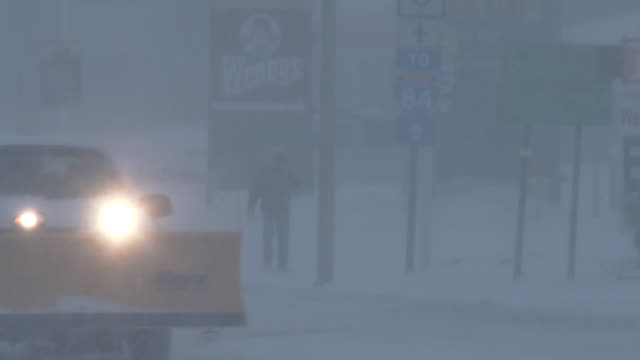 A man is barely visible through the heavy snow as he walks down the street in Waterbury Connecticut during an intense blizzard