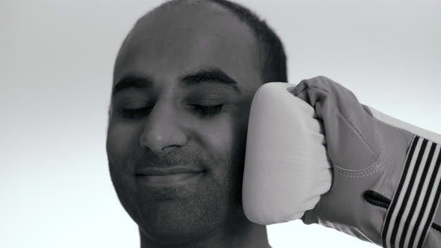 A man is being hit with a boxing glove in the face slow motion Sweden.