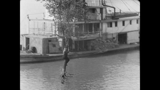 1928 a man (buster keaton) is blown through town on an uprooted tree - 1928 stock videos & royalty-free footage