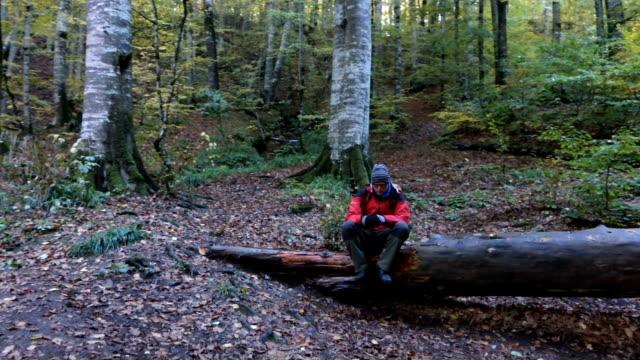 man is diep ademhalen terwijl staande op een boom in het bos in de herfst