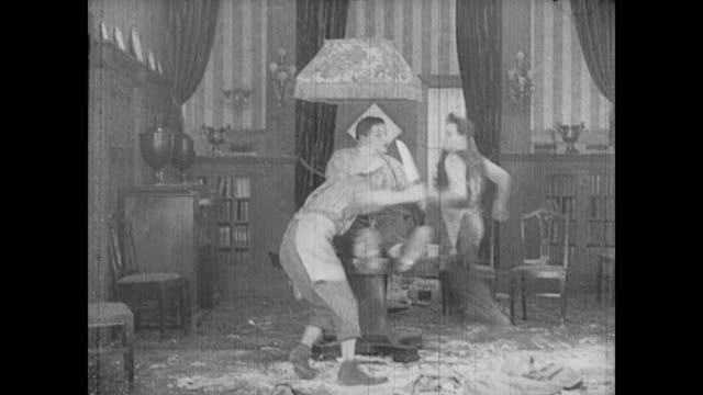 1917 man (buster keaton) is chased in circles around a table by a knife wielding chef as man (fatty arbuckle) sits and spins on the table - スラップスティックコメディ点の映像素材/bロール