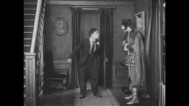 1921 man (buster keaton) is confused into acrobatics by costumed men - anno 1921 video stock e b–roll