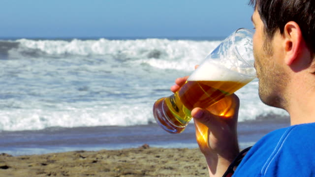 Man is drinking beer on a beach
