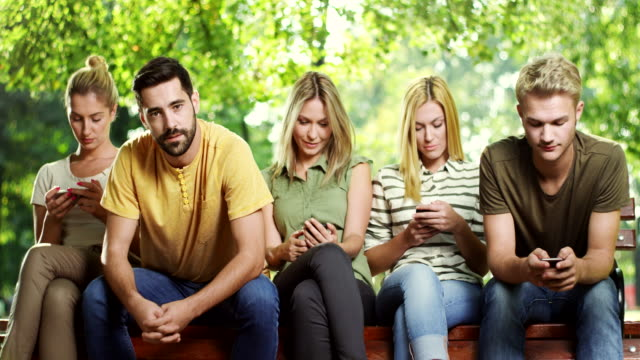 man is getting bored while all his friends looking at phone - assuefazione video stock e b–roll