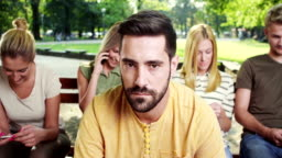 Man is getting bored while all his friends looking at phone