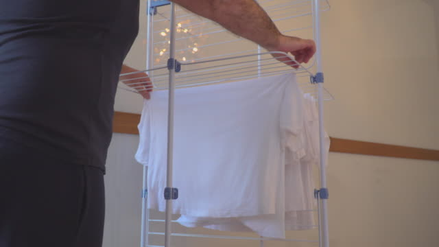 man is hanging washed laundry - asciugare video stock e b–roll