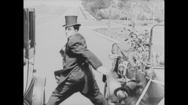 vidéos et rushes de 1920 man (buster keaton) is hit by a motorcycle while straddling two cars that are in motion - exploit sportif