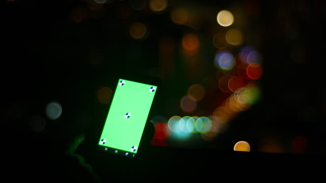 mann hält smartphone mit der green-screen am abend - projection screen stock-videos und b-roll-filmmaterial