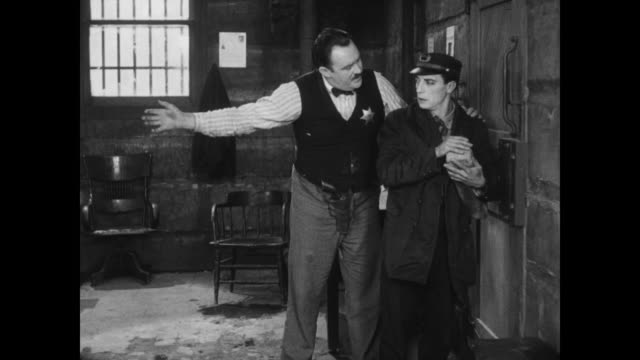 vídeos de stock e filmes b-roll de 1928 a man (buster keaton) is jailed after a failed escape from prison - 1928