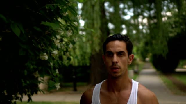 男は公園でジョギングします。 - アスレチック点の映像素材/bロール