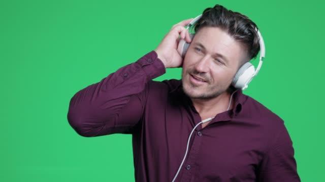 stockvideo's en b-roll-footage met man is luisteren muziek en dansen op groen schermachtergrond - in ear koptelefoon
