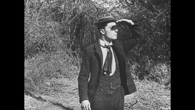 1921 man (buster keaton) is lost in the woods - searching stock-videos und b-roll-filmmaterial
