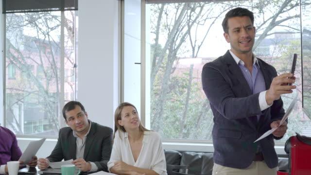 vídeos de stock, filmes e b-roll de o homem está a fazer conhecer os bons resultados da empresa para os seus colegas - colômbia