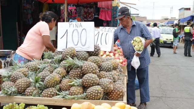 man is passing a pinapple and apple stand at a street market in piura, peru. - latin america stock videos & royalty-free footage