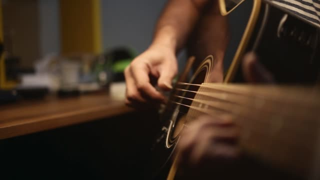 a man is playing guitar. close-up fingers and selective focus - musical instrument string stock videos & royalty-free footage