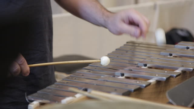 A man is playing on xylophone