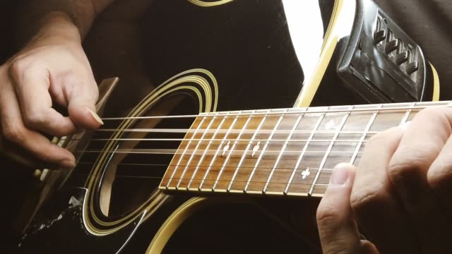 a man is playing slow motion acoustic guitar - musical instrument string stock videos & royalty-free footage