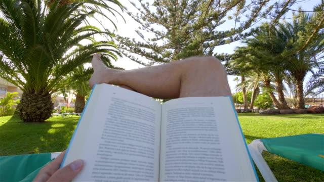 Man liest ein Buch auf einer Liege in einem tropischen Garten in 4 K-Slow-motion