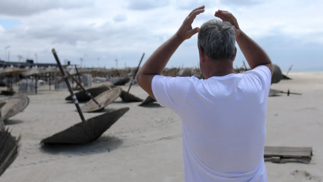 man is shocked while looking at the beach day after the storm - damaged stock videos & royalty-free footage