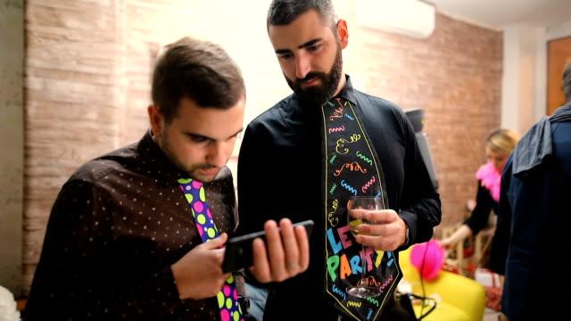 l'uomo sta mostrando qualcosa di interessante e divertente al suo amico. concetto di partito cravatte divertenti - shirt and tie video stock e b–roll