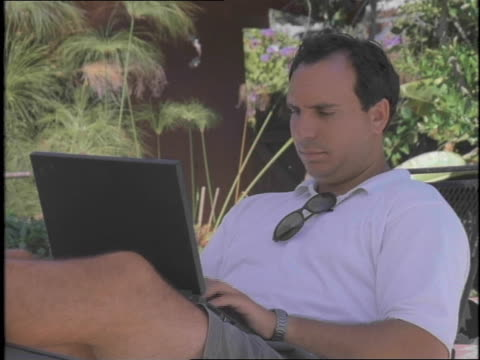 a man is sitting with his feet up and relaxing outdoors while working on laptop computer - dreiviertelansicht stock-videos und b-roll-filmmaterial