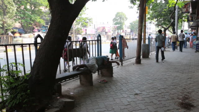A man is sleeping on a bench on the street in Kolkata (City of Joy)