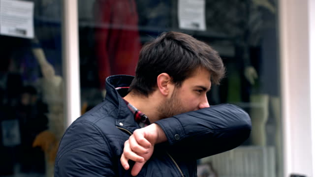 man is sneezing on public area. coronavirus symptoms. - sneezing stock videos & royalty-free footage