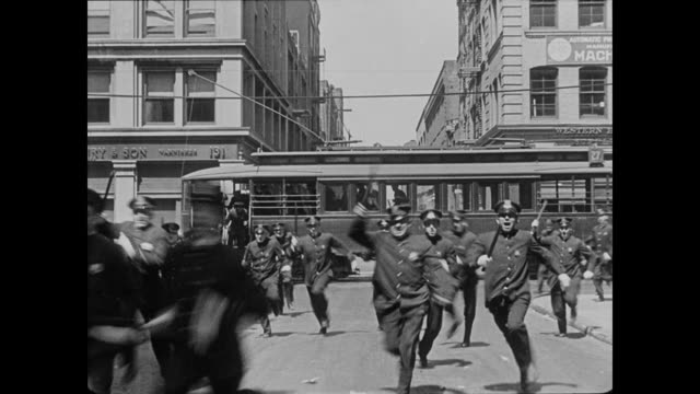 1922 man (buster keaton) is surprised when a group of policemen disembark from a trolley that appeared to be empty and chase him - thick stock videos and b-roll footage