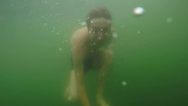 Man is onder water zwemmen in het meer.